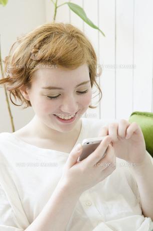 室内でスマートフォンを操作するハーフの女性の素材 [FYI01077218]