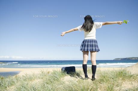 ビーチで両手を広げている制服姿の女の子の素材 [FYI01077219]