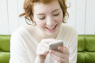 室内でスマートフォンを操作しながら笑うハーフの女性の素材 [FYI01077220]