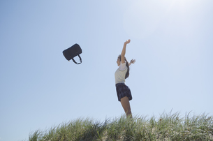 草むらに立ってカバンを放り投げている制服姿の女の子の素材 [FYI01077221]