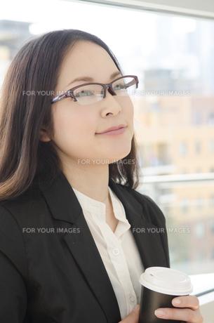 コーヒーカップを手に微笑む眼鏡をかけた女性の素材 [FYI01077229]