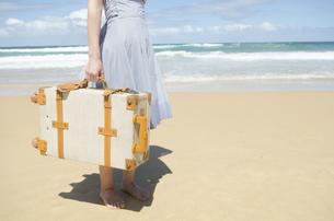 波打ち際をスーツケースを持って歩く女性の下半身の素材 [FYI01077231]