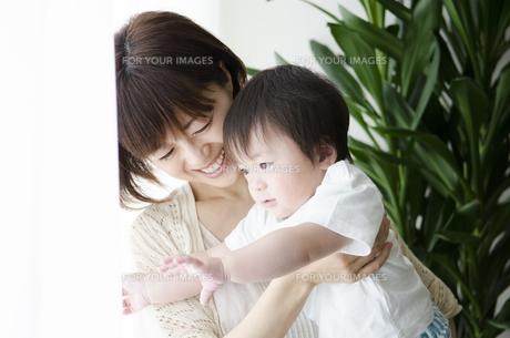 部屋の中で男の子を抱っこするお母さんの素材 [FYI01077234]