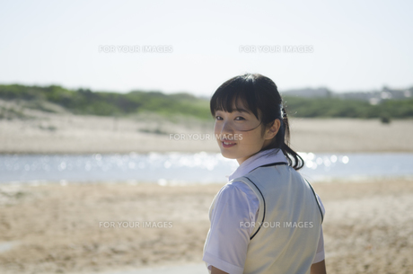 ビーチで振り返るポニーテールの制服姿の女の子の素材 [FYI01077235]