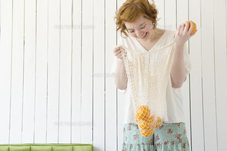 網の袋に入ったオレンジを見て笑うハーフの女性の素材 [FYI01077236]