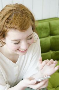 室内でスマートフォンを操作しながら笑うハーフの女性の素材 [FYI01077244]