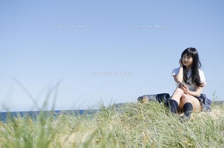 ビーチに座って音楽を聞いている制服姿の女の子の素材 [FYI01077247]