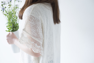 ポットに入った白いデイジーを持つ女性の横姿の素材 [FYI01077248]