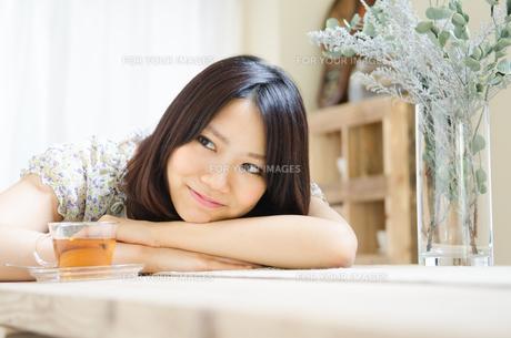 テーブルでリラックスしている女性の素材 [FYI01077250]