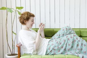 ソファに座ってスマートフォンを操作するハーフの女性の素材 [FYI01077251]