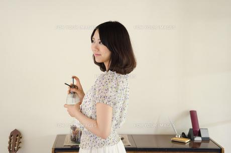 部屋の中でスプレーを手にしている女性の素材 [FYI01077252]