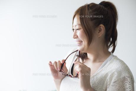 メガネを持って笑う女性の素材 [FYI01077253]