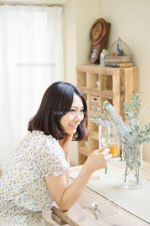 テーブルでお茶を飲んでいる女性の素材 [FYI01077254]