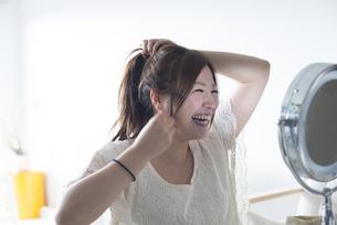 鏡を見ながら髪を結ぶ女性の素材 [FYI01077257]