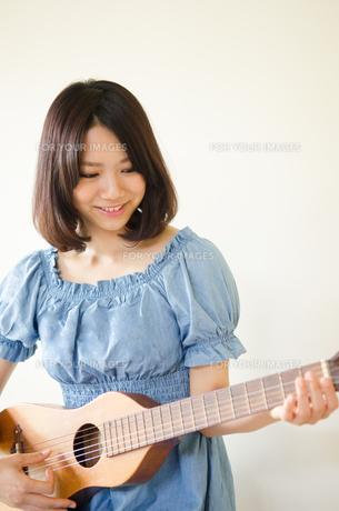 ギターを持っている笑顔の女性の素材 [FYI01077258]