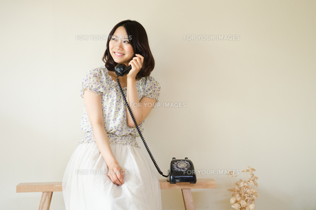 ベンチに座って黒電話で話す女性の素材 [FYI01077260]