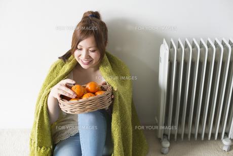 緑の毛布にくるまってみかんを触る女性の素材 [FYI01077261]