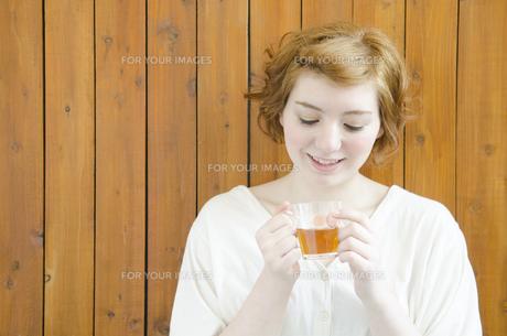 両手で持ったコップを見るハーフの女性の素材 [FYI01077262]