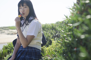 カラフルなアイスを食べる制服姿の女の子の素材 [FYI01077265]