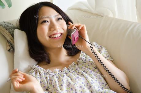 部屋の中で電話をしている笑顔の女性の素材 [FYI01077266]
