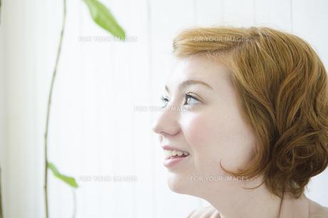 部屋の中で横を向くハーフの女性の素材 [FYI01077272]