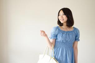 カバンを腕に掛けて笑う女性の素材 [FYI01077273]