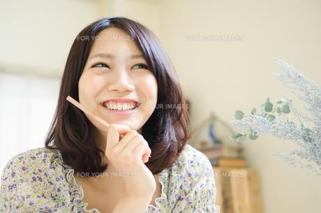 鉛筆を持って笑う女性の素材 [FYI01077275]