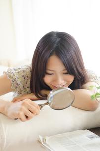 虫眼鏡で新聞を見ている女性の素材 [FYI01077277]