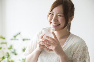 水の入ったコップを持って笑う女性の素材 [FYI01077278]