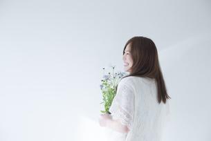 ポットに入った白いデイジーを持って笑う女性の素材 [FYI01077279]