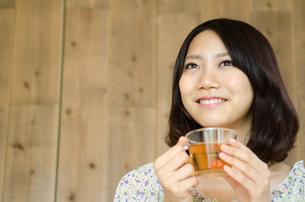 お茶の入ったグラスを持って笑う女性の素材 [FYI01077280]