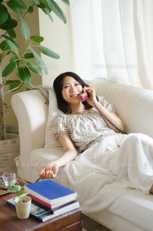 ソファに寝そべって電話をしている笑顔の女性の素材 [FYI01077281]