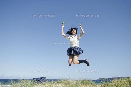 ビーチでジャンプする制服姿の女の子の素材 [FYI01077285]