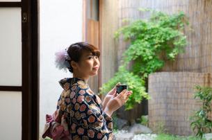 縁側に座ってお茶の入った湯のみを持つ着物姿の女性の素材 [FYI01077286]