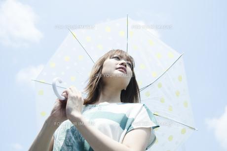 青空をバックに傘を差した女性の素材 [FYI01077290]