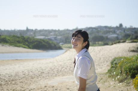 ビーチで笑うポニーテールの制服姿の女の子の素材 [FYI01077291]
