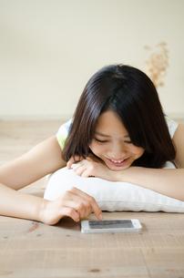 床に寝そべってスマートフォンを操作する女性の素材 [FYI01077294]
