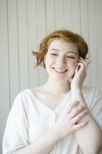 室内で電話で話しているハーフの女性の素材 [FYI01077298]