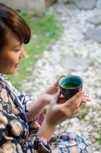 お茶の入った湯のみを持つ着物姿の女性の素材 [FYI01077302]