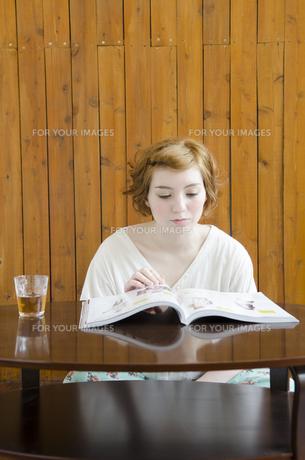 部屋の中で雑誌を読むハーフの女性の素材 [FYI01077305]