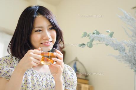 お茶の入ったグラスを持って笑う女性の素材 [FYI01077306]