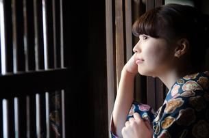 格子の窓から外を見る着物姿の女性の素材 [FYI01077310]