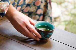 お茶の入った湯のみと女性の手の素材 [FYI01077311]