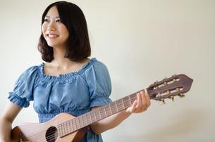 ギターを持っている笑顔の女性の素材 [FYI01077317]