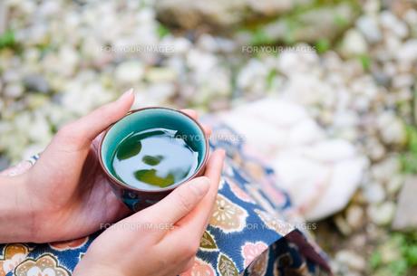 お茶の入った湯のみと女性の手の素材 [FYI01077318]