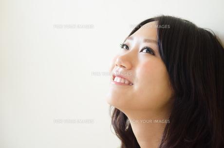 上を見上げて笑う女性の素材 [FYI01077320]