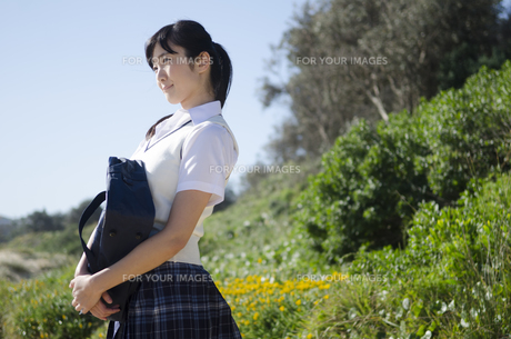 カバンを抱えて遠くを見る制服姿の女の子の素材 [FYI01077323]
