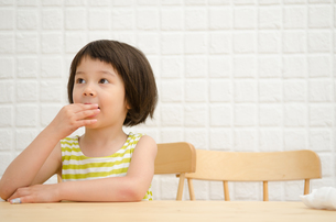 イスに座っておやつを食べる女の子の素材 [FYI01077325]