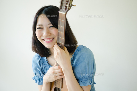 ギターを抱えている笑顔の女性の素材 [FYI01077326]