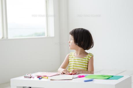 折り紙で遊びながら外を眺める女の子の素材 [FYI01077330]